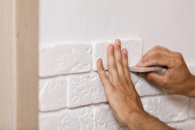 Constructeur professionnel collant des carreaux décoratifs sur le mur. travailleur monte la brique décorative sur le mur