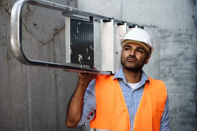 Constructeur professionnel exerçant son échelle en métal close up