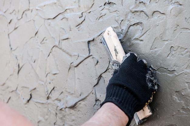 Constructeur professionnel moulant la texture décorative du plâtrage vénitien sur le mur avec du plâtre, pas de visage