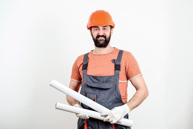 Constructeur professionnel en uniforme et casque. travailleur barbu tenant le plan avec le nouveau projet.