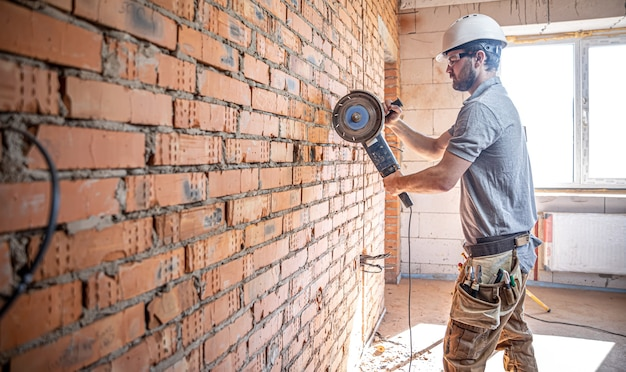 Un constructeur professionnel en vêtements de travail travaille avec un outil de coupe