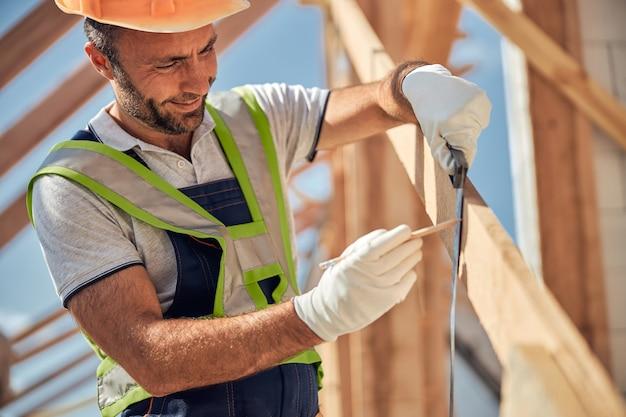 Constructeur ravi positif faisant la marque sur le faisceau