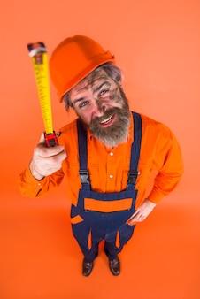 Constructeur avec ruban à mesurer. ouvrier du batiment. le travailleur utilise un ruban à mesurer. l'équipement du constructeur. appareil de mesure. constructeur en casque de protection. outils de réparation.