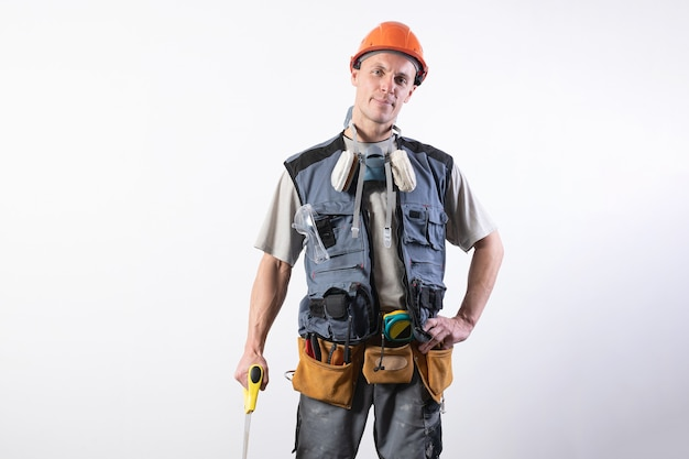 Constructeur avec une scie. en tenue de travail et un casque. sur un fond gris clair. pour n'importe quel but.