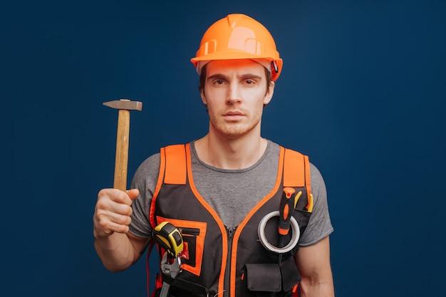 Constructeur sérieux dans un casque avec un marteau