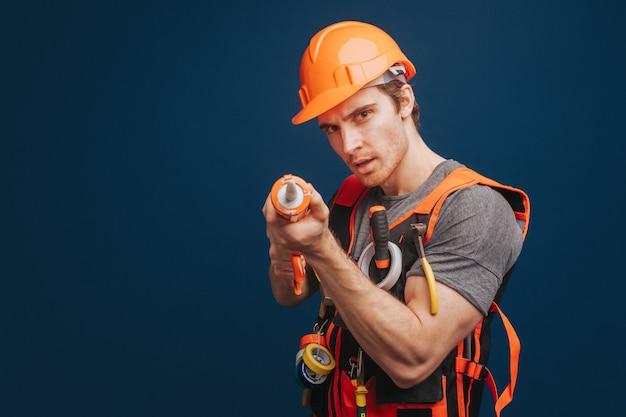 Le constructeur tient de l'adhésif de construction et vise la caméra
