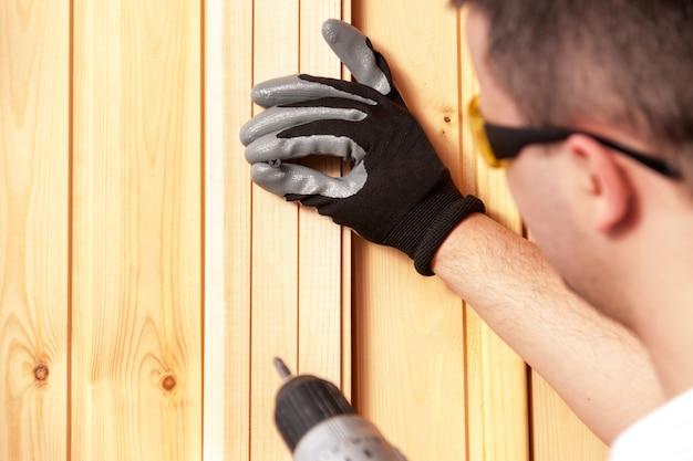 Le constructeur tient dans sa main un tournevis électrique sur le fond d'un mur de béton.