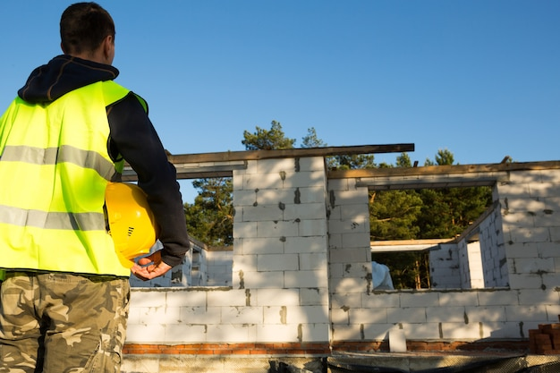 Le constructeur tient en main un casque protecteur jaune sur le chantier de construction