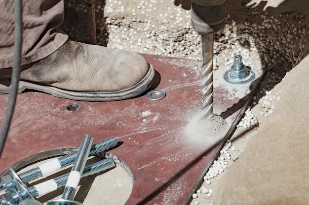 Le constructeur utilise une perceuse pour percer un béton