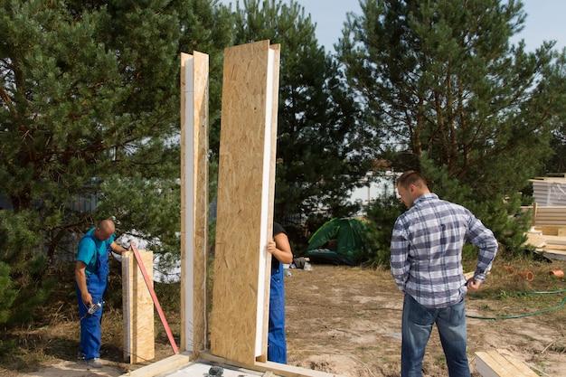 Constructeurs alignant des panneaux muraux en bois isolés surveillés par l'architecte ou le contremaître pendant qu'ils positionnent les unités de coin