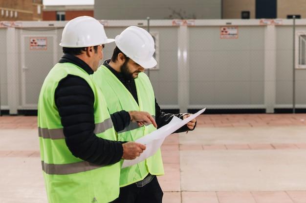Constructeurs discutant des brouillons