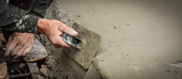 Les constructeurs enduisent les murs du sol avec netteté.