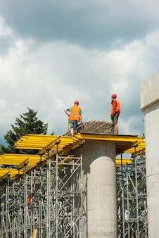 Les constructeurs installent des structures en béton armé sur des colonnes en béton lors de la construction d'un pont routier.