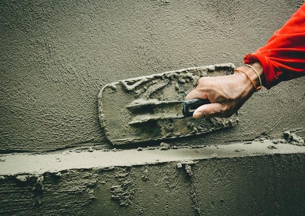 Les constructeurs plâtrent les murs de la maison avec soin.