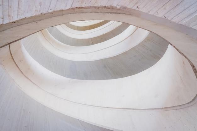 Construction en béton circulaire, fond de géométrie abstraite de tons clairs et lumineux.