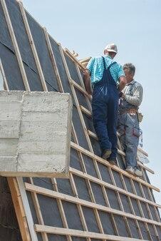 Construction de condo avec des travailleurs sur le toit