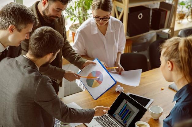 Construction d'équipe. groupe de jeunes professionnels ayant une réunion. un groupe diversifié de collègues discute de nouvelles décisions, plans, résultats, stratégie. créativité, lieu de travail, affaires, finance, travail d'équipe.