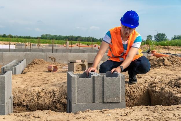 Construction de la fondation d'un bâtiment avec coffrage perdu par un jeune ingénieur en construction.