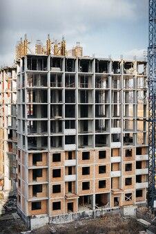 Construction d'un gratte-ciel moderne avec des grues au centre de la métropole