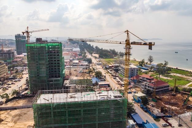 Construction high-rise building par grue de construction dans la ville près de la mer. construction d'hôtels coûteux dans la station balnéaire de sihanoukville au cambodge. beaucoup de grues de construction. construction à l'échelle.