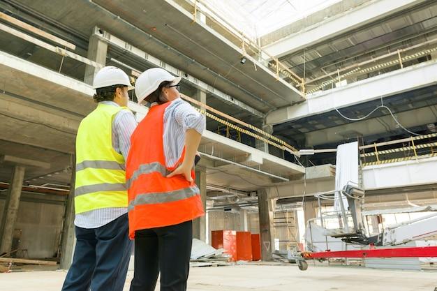 Construction, homme et femme constructeurs sur chantier, équipe d'industriels