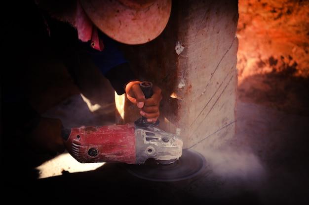 Construction homme ouvrier tenant une scie électrique couper le béton