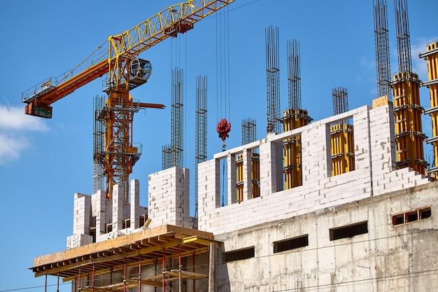Construction d'un immeuble de grande hauteur, formation de supports en ciment et opération d'une grue sur ciel bleu, mise au point sélective