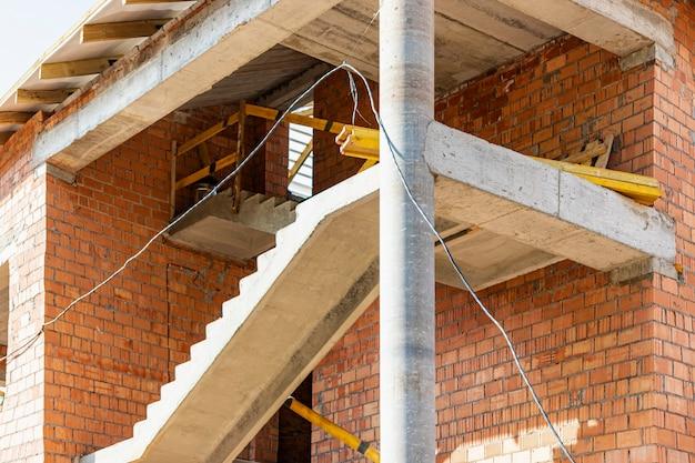 Construction d'un immeuble de plusieurs étages en brique rouge. l'utilisation d'échafaudages lors de la construction d'une maison. construction industrielle et civile. escalier en béton armé.