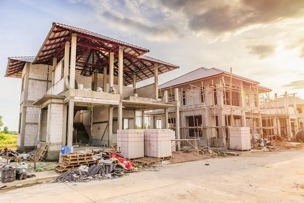 Construction nouvelle maison résidentielle en cours sur chantier avec nuages et ciel bleu