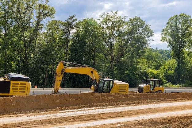 En construction d'une nouvelle route asphaltée. les excavatrices, niveleuses travaillant sur le nouveau chantier de construction de routes