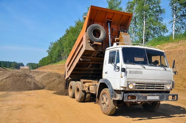 Construction d'une nouvelle route un camion-benne décharge du sable