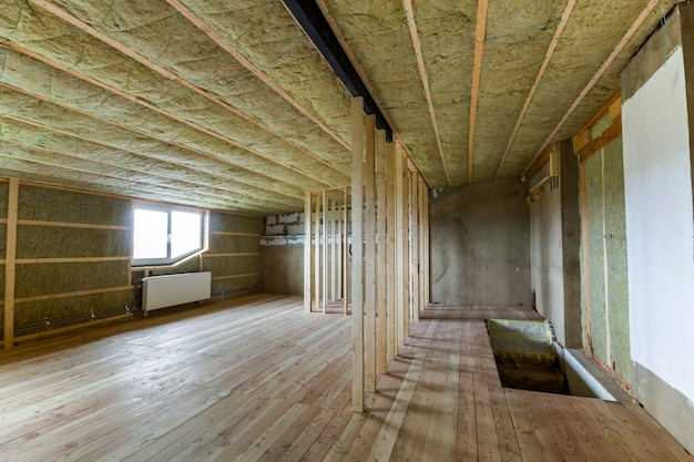 Construction et rénovation d'une grande pièce vide spacieuse et lumineuse avec parquet en chêne, murs et plafond isolés à la laine de roche, radiateurs de chauffage sous les fenêtres basses du grenier et ossature bois pour les futurs murs.