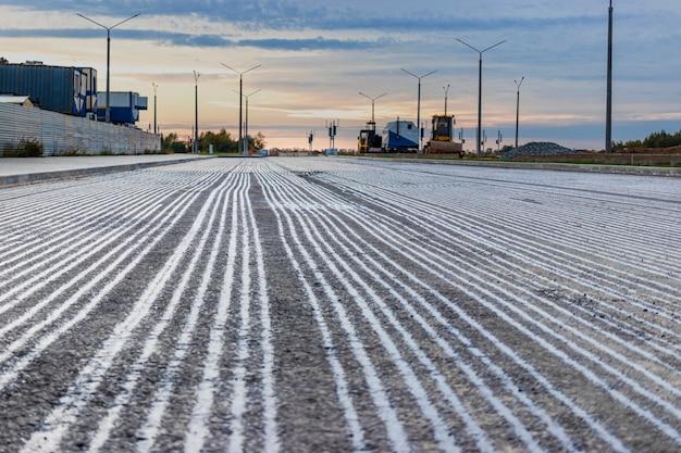 Construction ou réparation de routes - pose d'une nouvelle couche d'asphalte, recouvrant l'ancienne couche d'asphalte de bitume pour améliorer l'adhérence. travaux de rénovation le soir et la nuit.