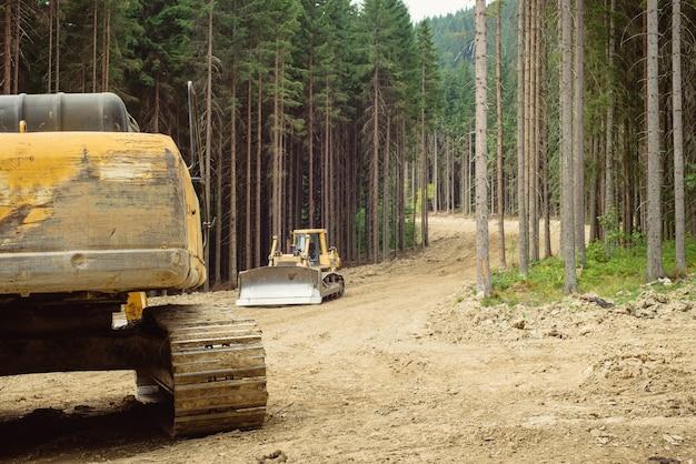 Construction de routes de montagne avec des excavatrices et de la machinerie lourde. déforestation sur la pente