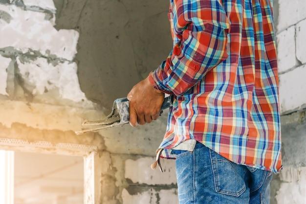 Construction sous bâtiment avec maçon plâtrer le béton au mur de briques