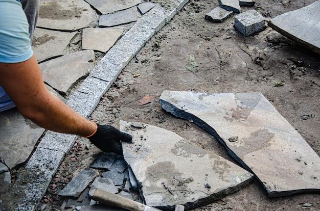 Construction de trottoir près de la maison. le maçon place des pavés en béton pour la construction d'un trottoir