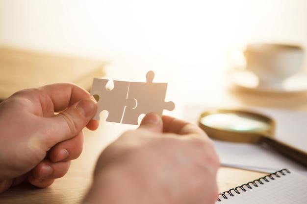 Construire un succès commercial. concept pour le conseil, le marketing, les affaires, la stratégie et la planification. les mains masculines avec des puzzles