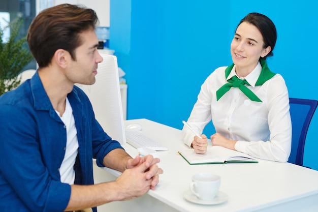 Consultant dame souriante communiquant avec le client