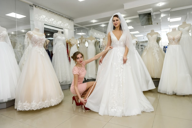Un consultant en mariage aide la mariée à ajuster sa robe de mariée dans un salon