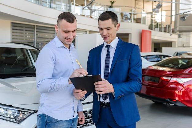 Un consultant signe les documents avec l'acheteur sur la voiture