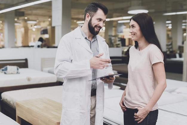 Une consultante en orthopédie l'aide à choisir le bon matelas.