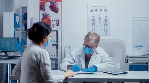 Consultation d'un médecin pendant la crise sanitaire du covid 19, médecin et patient portant des masques, parlant à travers un mur en plexiglas. consultation médicale dans le concept d'équipement de protection shot de sras-cov-2 globa