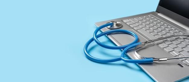 Consultation médicale en ligne, hôpital virtuel et thérapie en ligne. stéthoscope se trouve sur le clavier d'ordinateur portable sur fond bleu