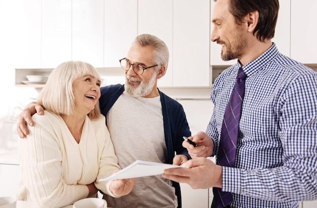 Consultation avec un professionnel. rencontre d'un couple de personnes âgées harmonieux et optimiste amical avec un conseiller financier et le consulter lors du choix de la variante d'investissement