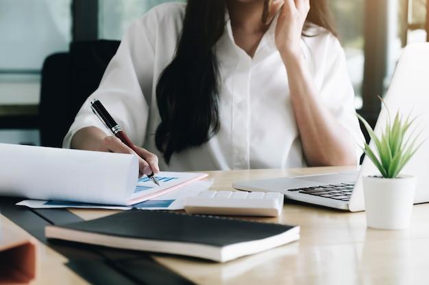 Consultez le concept financier. femme d'affaires pointant sur papwework et à l'aide de téléphone.