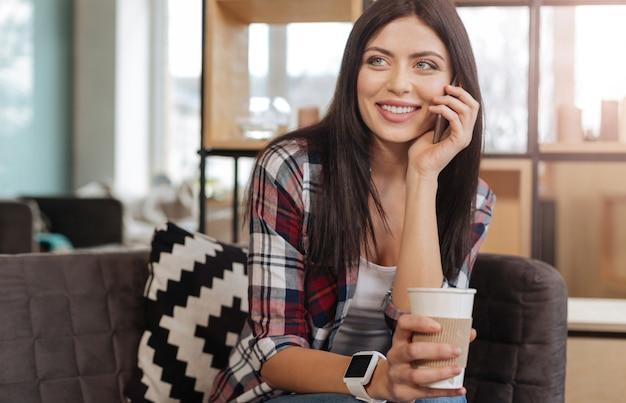 En contact. enthousiaste ravie jolie femme parlant au téléphone avec quelqu'un et appréciant son thé tout en étant de bonne humeur