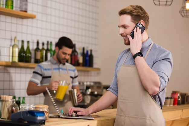 En contact. heureux bel homme positif tenant son smartphone et passer un appel en se tenant debout devant l'ordinateur portable