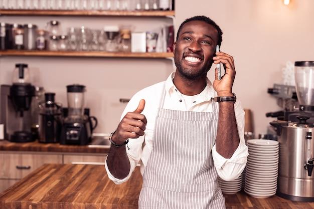 En contact. joyeux homme heureux souriant tout en ayant une conversation téléphonique
