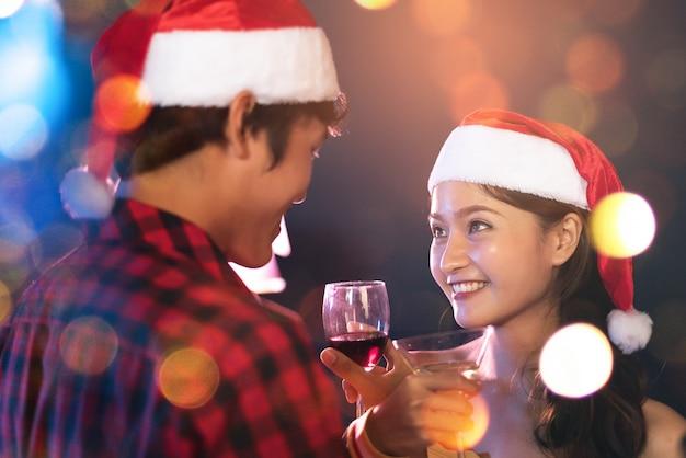 Contact des yeux d'amoureux asiatiques regardant et souriant les uns aux autres dans le pub