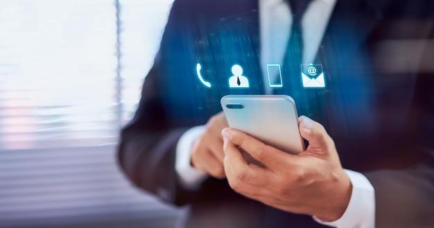 Contactez-nous concept, main d'homme d'affaires tenant le smartphone avec le centre d'appel du service client icône.